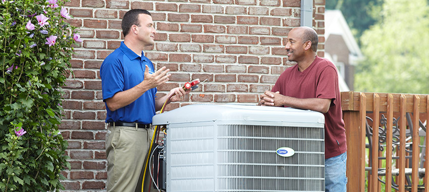 HVAC technician teaching a customer about his new Carrier air conditioner